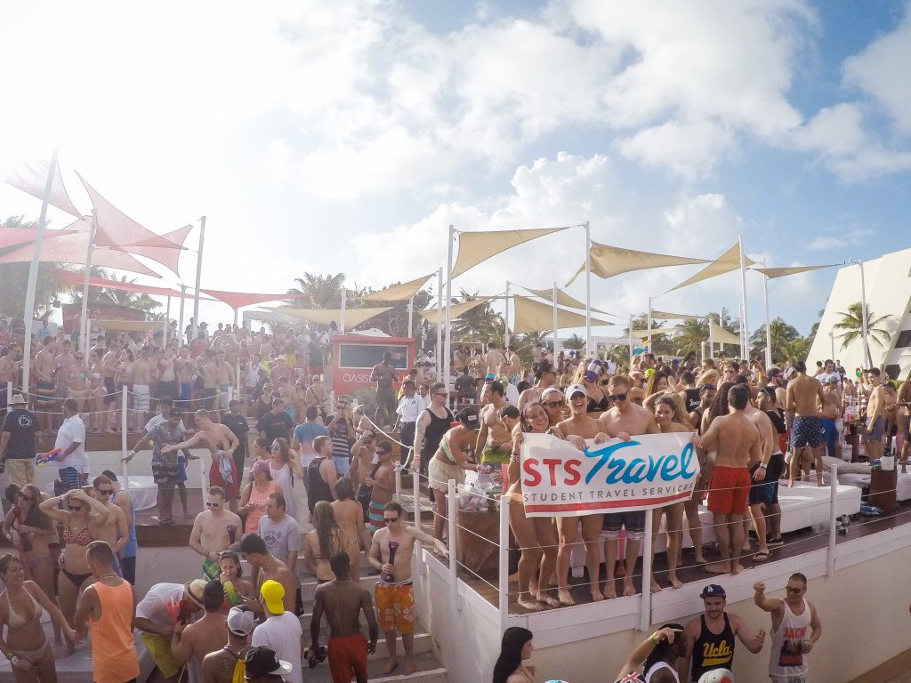 Oasis Cancun Lite holding an STS Travel Banner